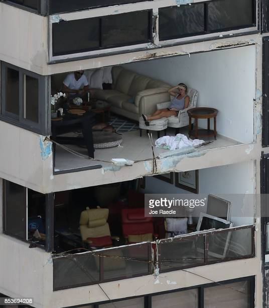People sit in their apartment with the window blown out by the winds of Hurricane Maria as it passed through the area last week on September 25 2017...