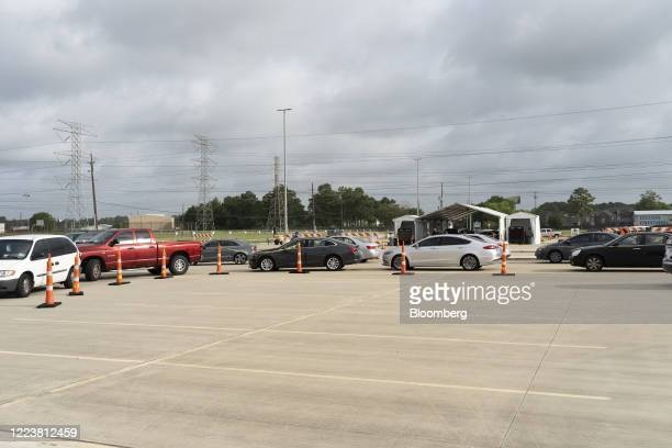 People sit in their vehicles while waiting in line to enter a Harris County Covid-19 drive-thru testing site at Ken Pridgeon Stadium in Houston,...