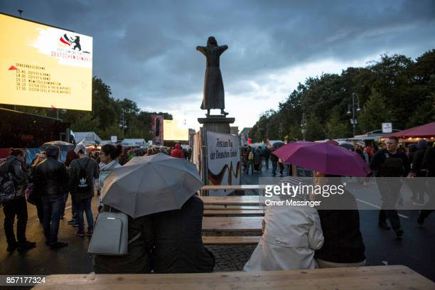 People sit in under umbrellas at an amusement area set up along 17th of June Street in Tiergraten Park near the Brandenburg Gate on German Unity Day...