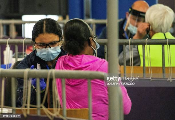 People sit in vaccination booths, to receive the Pfizer-BioNTech COVID-19 Vaccine at Fenway Park in Boston, Massachusetts on January 29, 2021. -...