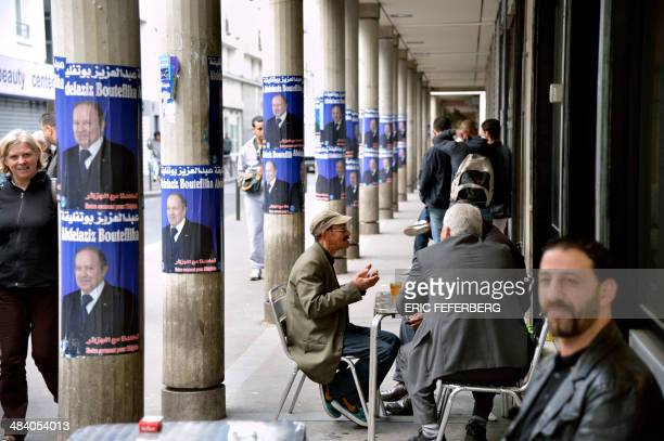 People sit near campaign posters for Algerian president Abdelaziz Bouteflika at a cafe terrasse in a street of the 'Goutte d'Or' district of Paris on...