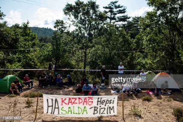 People sit next to a banner reading Ida mountains and Lake Salda are all ours during a piano recital by Turkish pianist and composer Fazil Say...