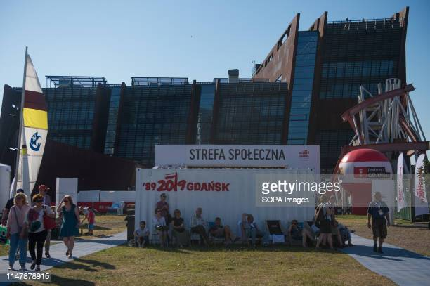 People sit next to a container with the logo of the 30th Anniversary of free elections in Poland during the week long celebrations. Gdansk, in the...