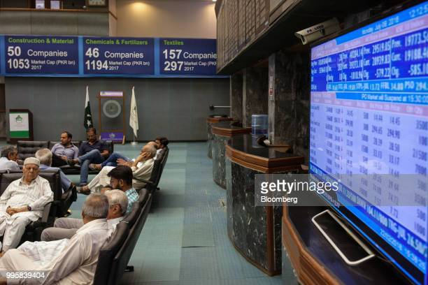 People sit next to a monitor displaying stock prices during a trading session at the Pakistan Stock Exchange in Karachi Pakistan on Monday July 9...