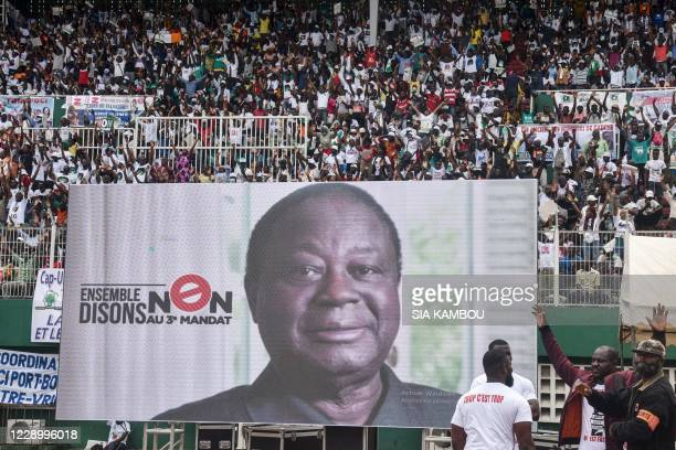 People sit next to a screen showing a picture of Ivory Coast's former president and Democratic Party of Ivory Coast African Democratic Rally...