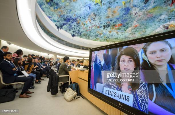 People sit next to a screening bearing a picture of US Ambassador to the United Nations Nikki Haley addressing a session of United Nations Human...