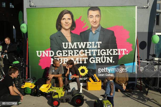People sit next to an election campaign billboard that shows German Greens Party colead candidates Cem Oezdemir and Katrin GoeringEckardt outside a...