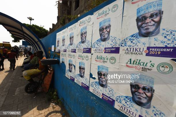 People sit next to campaign posters for Nigerian presidential candidate of the opposition People's Democratic Party Atiku Abubakar pasted at a bus...