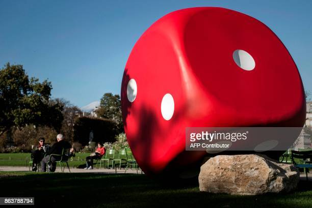 People sit next to the artwork 'The Misthrown Dice' by Gilles Barbier displayed at the Jardin des Tuilleries garden as part of the Paris...