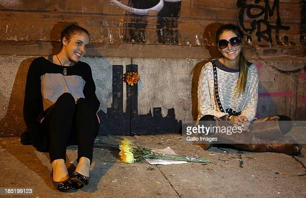 People sit next to the latest Banksy piece on October 15 2013 in New York City United States The graffiti artist who is in New York for the month of...