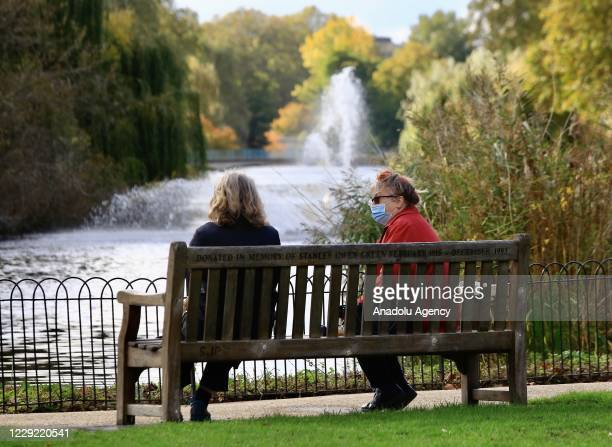 People sit on a bench at Saint James Park during autumn season in London, United Kingdom on October 22, 2020.