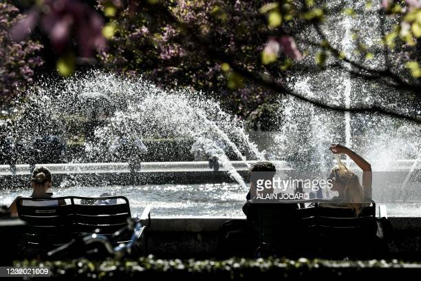 People sit on a bench in front of the fountain in the gardens of the Palais Royal in Paris, on March 30 during a sunny spring day.