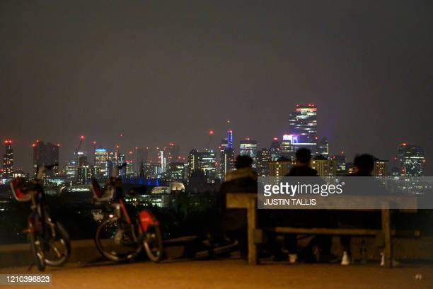People sit on a bench looking out at the view of the London skyline at night on Primrose Hill in London on April 18 during the novel coronavirus...