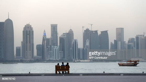 People sit on a bench on the corniche in the Qatari capital Doha on July 2 2017 / AFP PHOTO / STR