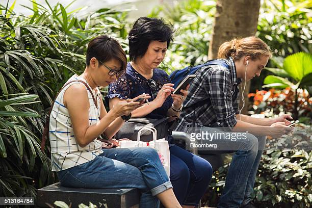 People sit on a bench using mobile phones on Orchard Road in Singapore on Monday Feb 29 2016 Singapore's Infocomm Development Authority plans to...