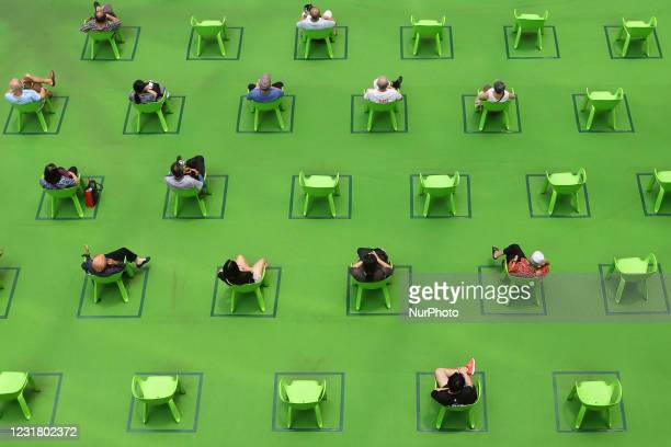 People sit on a chair marked out to keep social distancing amid the COVID-19 pandemic on March 19, 2021 in Singapore.