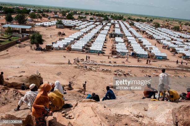 People sit on a hill facing an IDP camp as they wait for cellphone calls while herders return with their livestock from the outskirts of Pulka before...