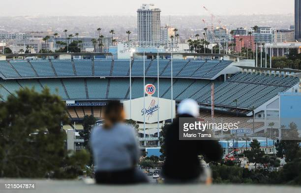 People sit on a hill overlooking Dodger Stadium on what was supposed to be Major League Baseball's opening day, now postponed due to the coronavirus,...