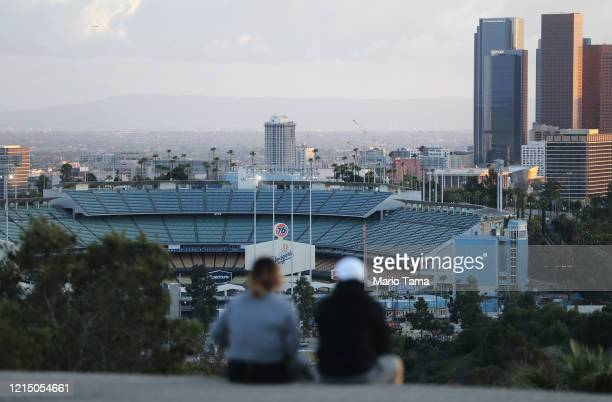 People sit on a hill overlooking Dodger Stadium on what was supposed to be Major League Baseball's opening day now postponed due to the coronavirus...