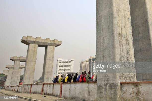 People sit on a ledge between mono rail line pillars under construction in Lagos Nigeria on Saturday Feb 16 2019 A lastminute delay of Nigerias...