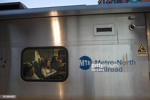 People sit on a MetroNorth Railroad train at the Yonkers Terminal in Yonkers New York US on Thursday Sept 19 2013 MetroNorth Railroad a subsidiary of...