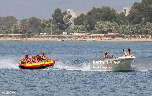 People sit on a sea chariot as it pulled by a motor boat in Izmir Turkey on July 25 2017 In Summer's extreme hot days people try to cool themselves...