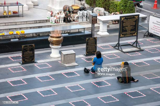 People sit on a social distancing square while praying in front of a shrine near Ratchadamri Road. The Thai government has applied social distancing...