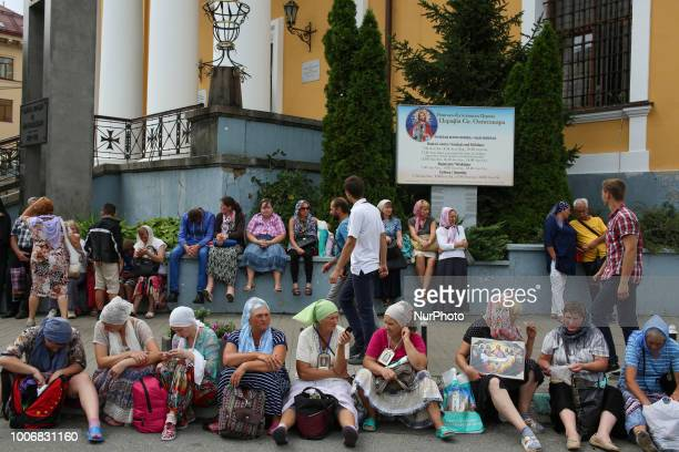 People sit on a stairs of Catholic church as Ukrainian Orthodox priests and believers take part in religious procession after a prayer service in...