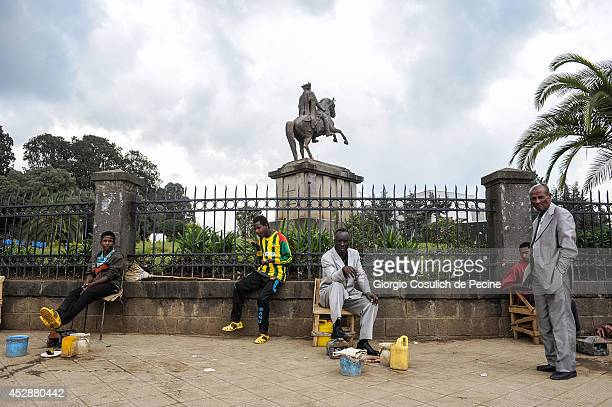 People sit on a wall in the background of the statue of Emperor Menelik II on July 01 2014 in Addis Ababa Ethiopia The Ethiopian government has...
