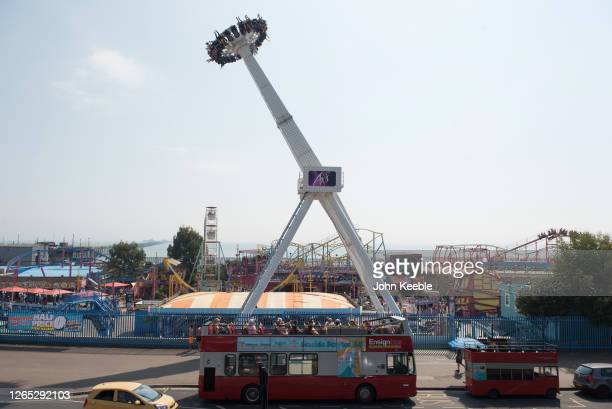 People sit on an open top bus as people enjoy the Axis ride at Adventure Island theme park on August 11, 2020 in Southend on Sea, England. Parts of...