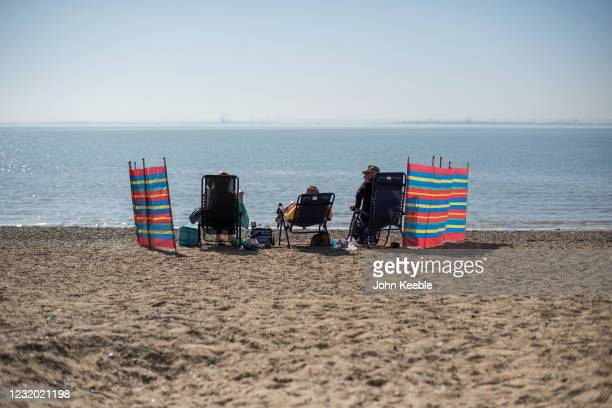 People sit on beach surrounded by wind breakers on March 30, 2021 in Southend, United Kingdom. Despite todays temperature heading towards 24 degrees,...