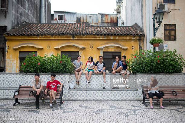 People sit on benches and a wall near Senado Square in Macau China on Wednesday July 16 2014 Las Vegas Sands Corp the worlds largest casino operator...
