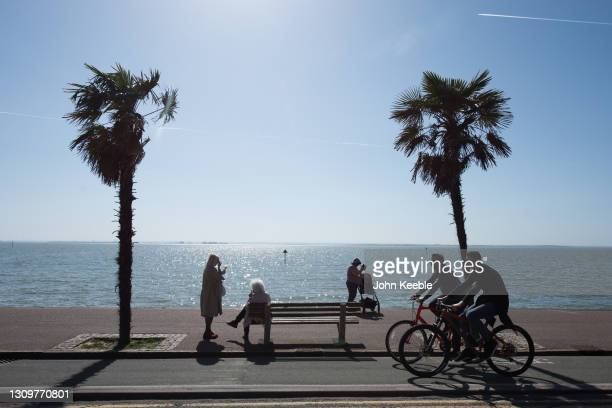 People sit on benches as cyclists pass by on the promenade beside the beach in the warm weather on March 29, 2021 in Southend, England. Today the...
