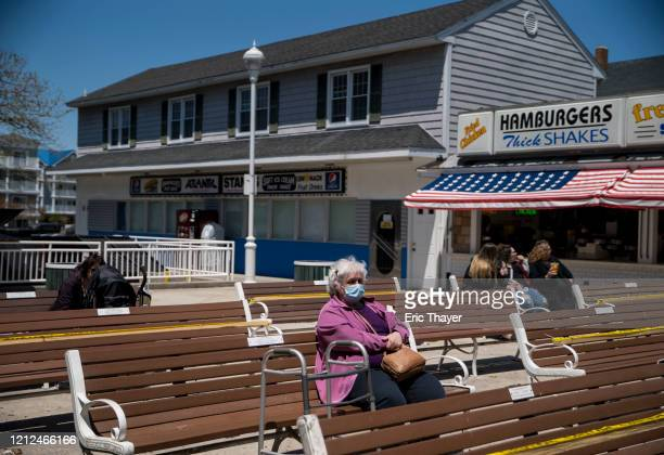 People sit on benches at the boardwalk as the area reopens from the coronavirus pandemic on May 10 2020 in Ocean City Maryland A popular summer...