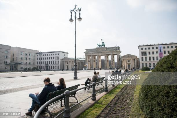 People sit on benches in front of Brandenburger Gate in Berlin on March 24, 2021.