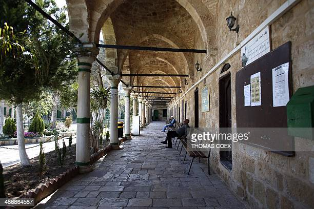 People sit on benches in the courtyard of the AlJazzar mosque in the ancient Mediterranean port town of Akko north of Haifa Israel on April 26 2014...