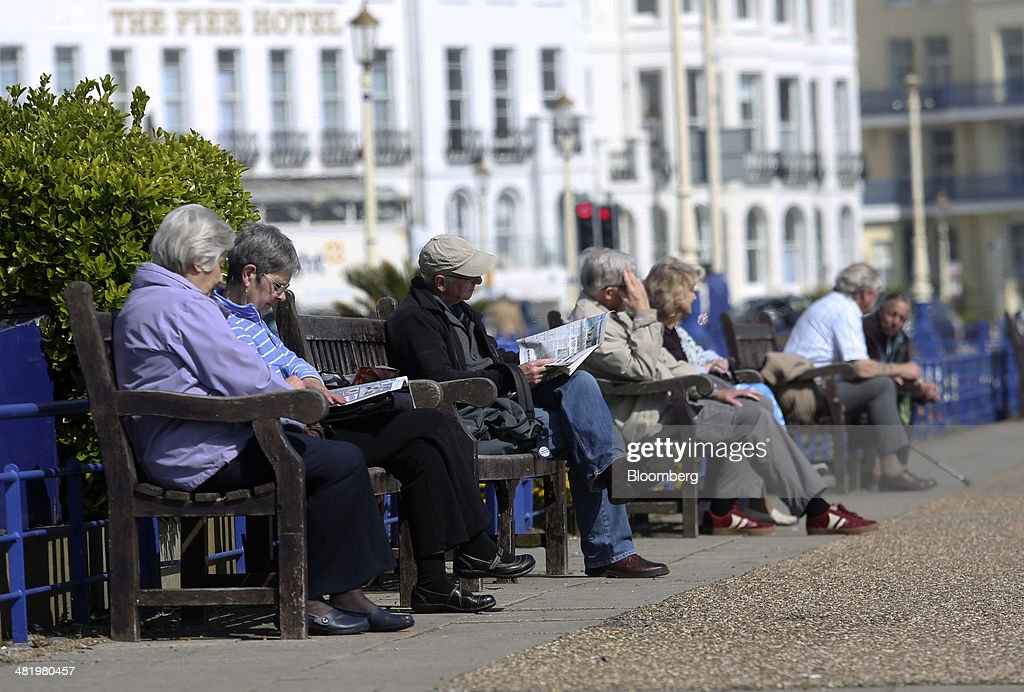 People sit on benches on the beachfront promenade near Eastbourne Pier in Eastbourne, U.K., on Tuesday, April 1, 2014. Pensioners and savers have seen returns on their money shrink since the financial crisis drove interest rates to a record low. Photographer: Chris Ratcliffe/Bloomberg via Getty Images