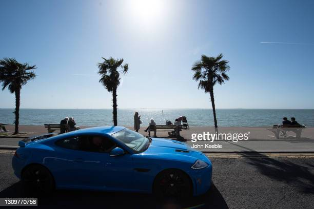 People sit on benches to enjoy the warm weather as a Jaguar XKR-S sports car passes by on the promenade beside the beach in the warm weather on March...