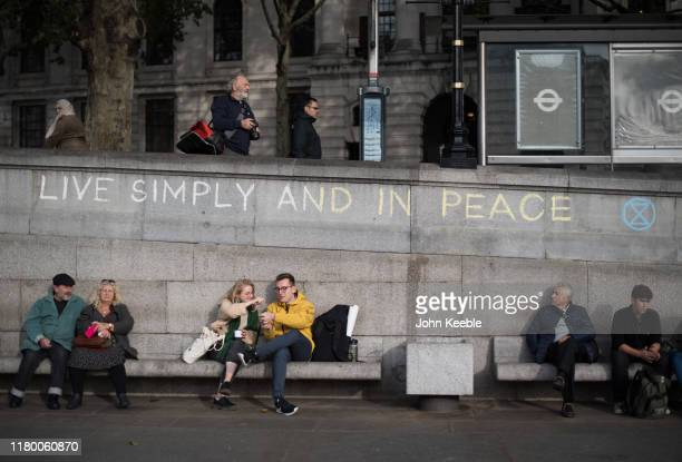 People sit on benches under graffiti saying Live simply and in peace as Extinction Rebellion Protesters camp at Trafalgar Square on October 09 2019...