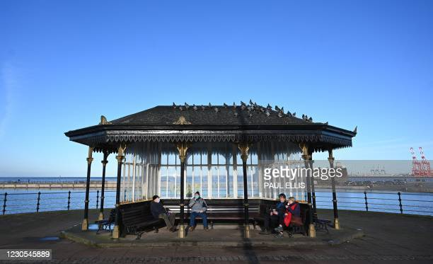 People sit on benches wearing masks because of the coronavirus pandemic on the promenade in New Brighton, northwest England, on January 12, 2021. -...