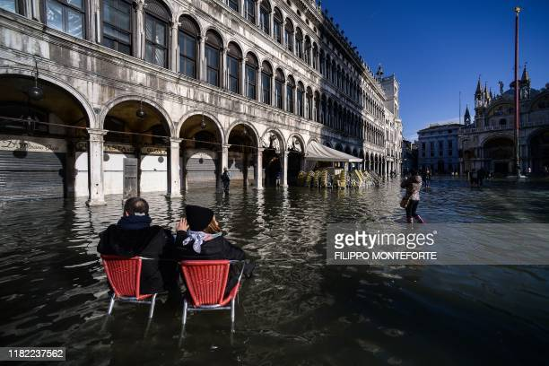 TOPSHOT People sit on bistro chairs in the middle of the flooded St Mark's Square on November 14 2019 in Venice Much of Venice was left under water...