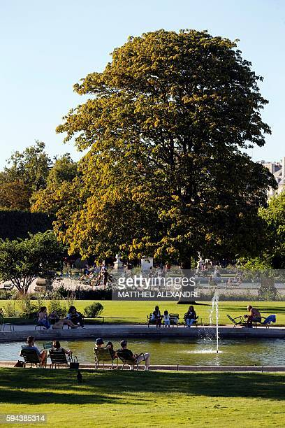 People sit on chairs around a fountain at the Jardin des Tuileries in Paris on August 23 2016 / AFP / MATTHIEU ALEXANDRE