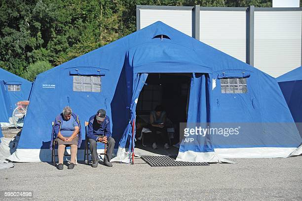 People sit on chairs outside tents of a temporary camp in Pescara del Tronto on August 25 a day after a 6.2-magnitude earthquake struck the region...