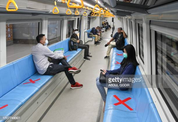 People sit on designated areas decided by red cross marks to ensure social distancing inside a light rapid transit train in Palembang, South Sumatra...