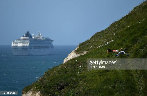 People sit on grass on a cliff as a Cruise ship sits at anchor in the English Channel at the popular tourist spot Durdle Door near West Lulworth on...