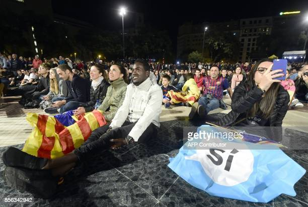 People sit on Plaza Catalunya square in Barcelona waiting for polls results after the closing of polling stations on October 1 2017 Spanish riot...