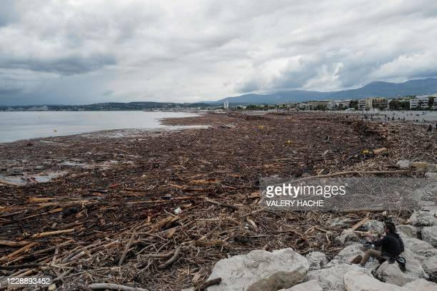 People sit on rocks near tree branches after the Storm Alex in Saint-Laurent-du-Var, on October 4 after extensive flooding caused widespread damage...