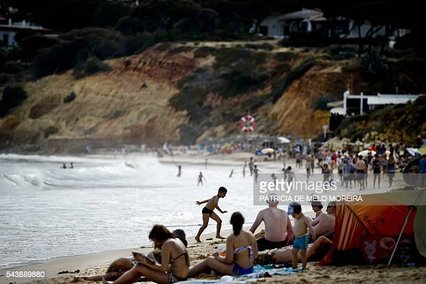 People sit on Santa Eulalia beach at Albufeira Loule southern Portugal on June 10 2016 Instability and violence in the Mediterranean's former top...