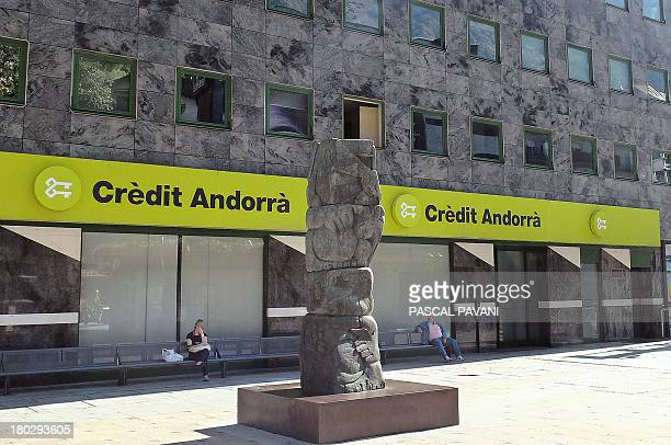 People sit on September 10 2013 outside a branch of the Credit Andorra bank in the city of AndorralaVielle principality of Andorra AFP PHOTO PASCAL...