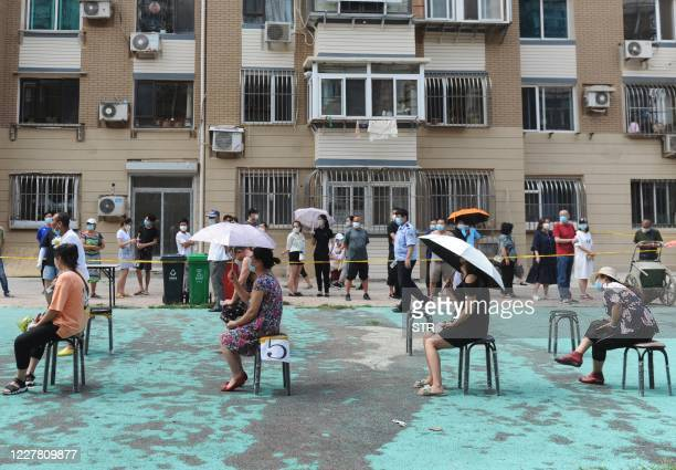 People sit on socially distanced chairs as they wait to undergo COVID-19 coronavirus tests at a makeshift testing centre in Dalian, in China's...